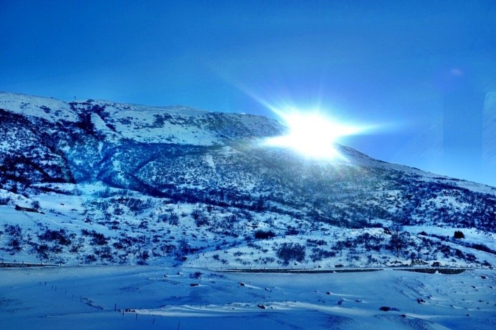 Snowy landscape on top of the Oberalppass as seen from the Glacier Express. The sun is bright