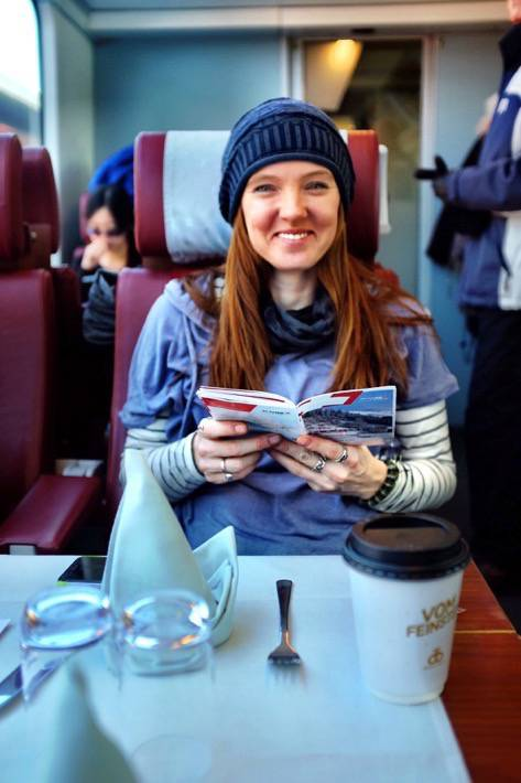 Sarah smiles while she reads a brochure in the Glacier Express