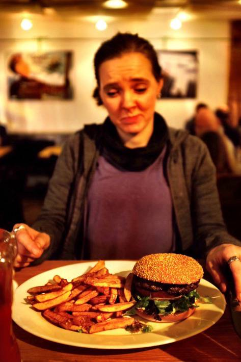 Sarah looks down at her Burger she had in the Bubble in Zermatt