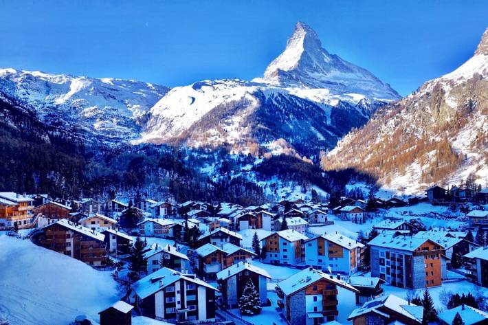 The mount Matterhorn is in the background and Zermatt is on the foreground. Snowcovered