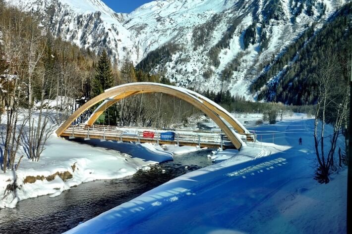 A wooden bridge with snowy mountains in the background