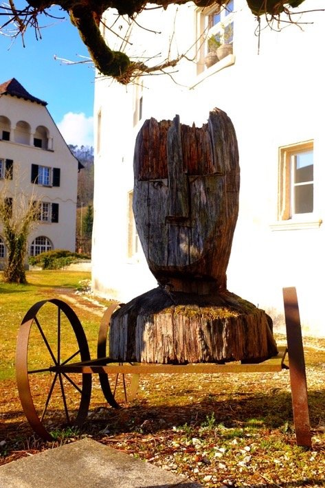Wooden sculpture of a head in front of the castle Zwingen