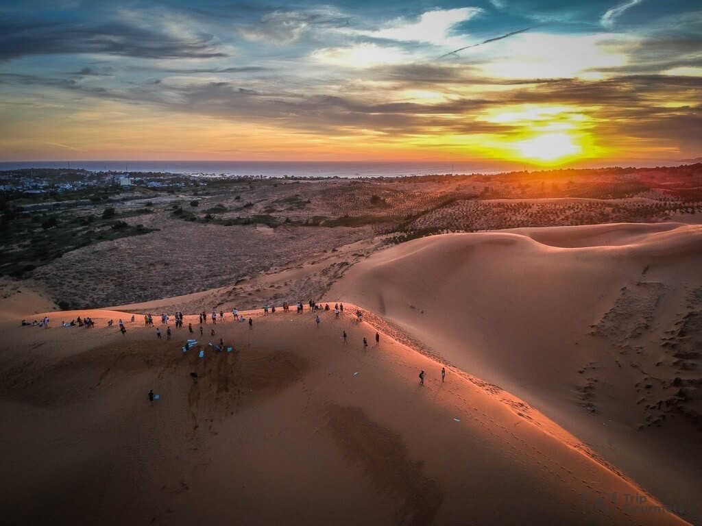 Things to do in Mui Ne Muine red dunes desert sand sunset clouds sea people