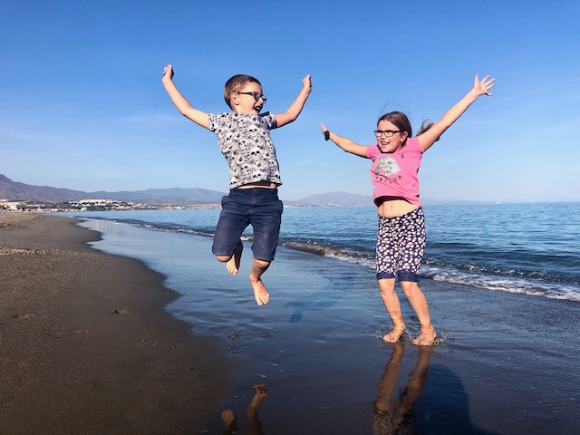 Children jumping on beach in front of sea