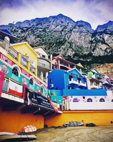 brightly coloured buldings with mountain from beach in Catalan Bay Gibraltar holiday