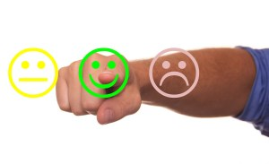 A person pointing a finger at a smiley face symbol