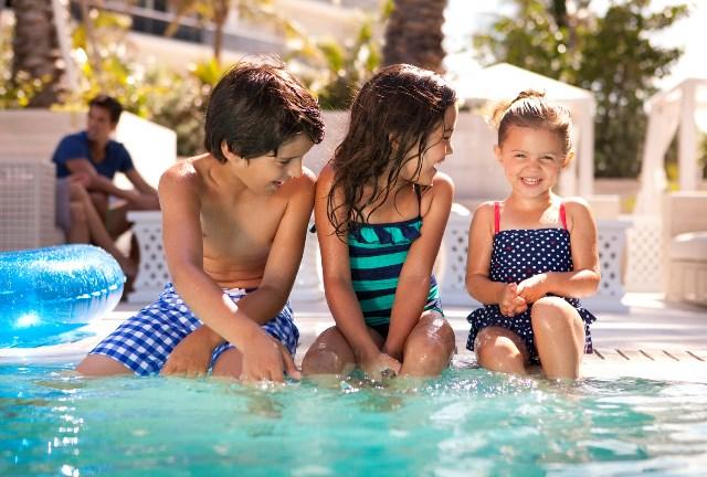 three kids at a swimming pool in bali