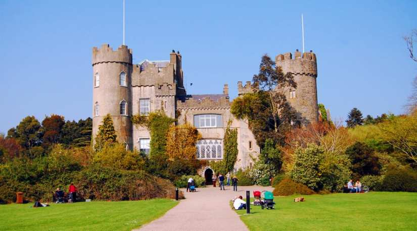 a family sit on the grass in front of Malahide Castle