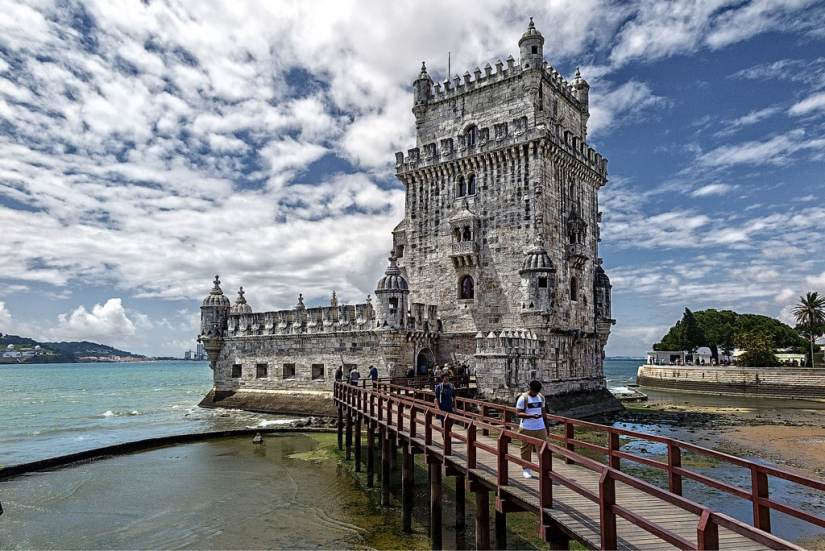 2 men are walking from belém tower