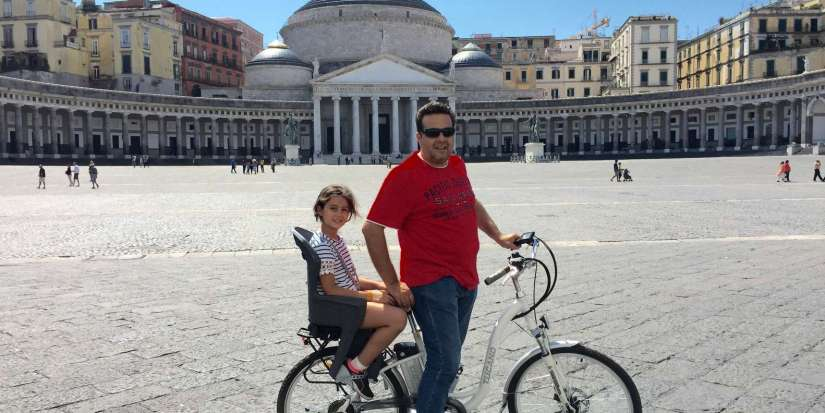 father and kids on electric bike around naples