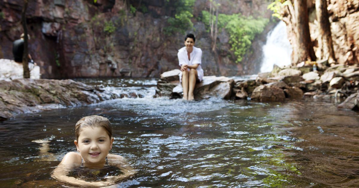 A little girl swims at Florence Falls in Litchfield National Park