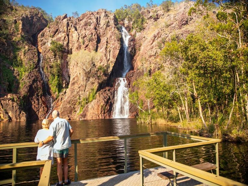 a senior couple stand in front of Florence Falls in Litchfield National Park