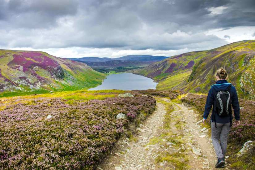 a girl is walking at Cairngorms National Park