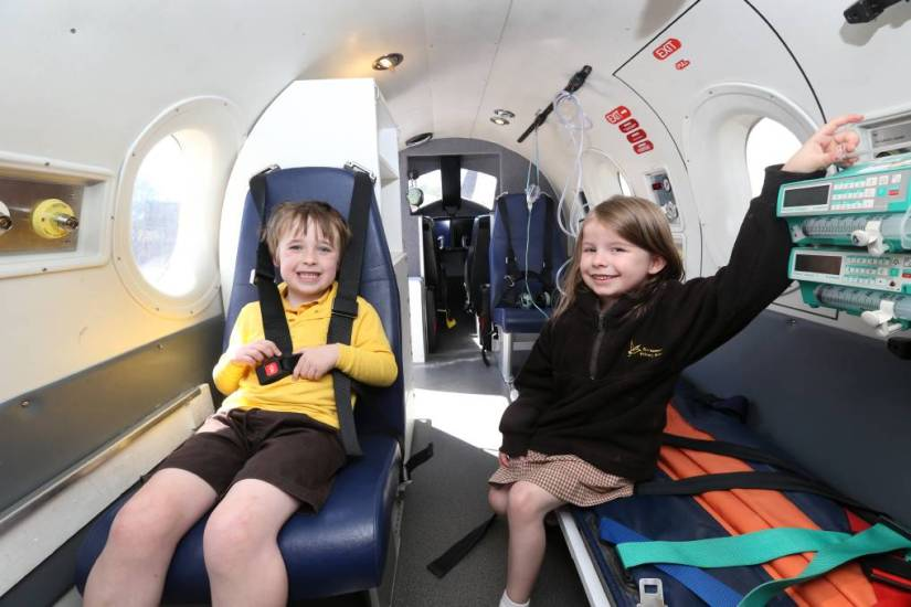 2 kids are sitting inside the plane at The RFDS Darwin Tourist Facility