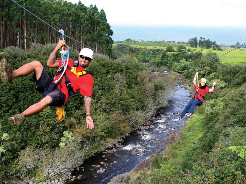 2 people are riding zipline at Umauma Falls