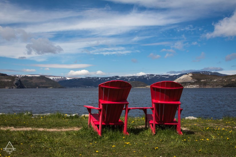 Two Red Chairs Overlooking Water in Newfoundland
