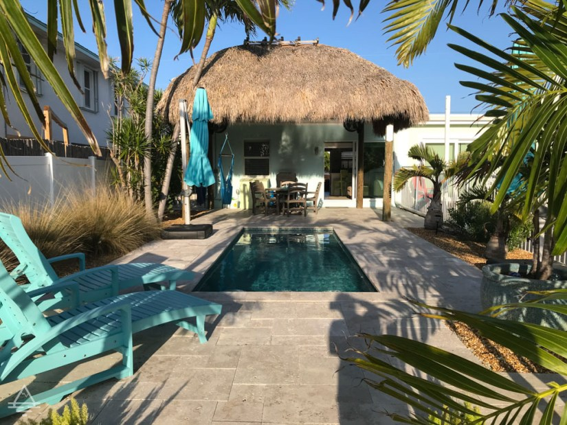 Outdoor living space with pool, chairs, tiki pavilion