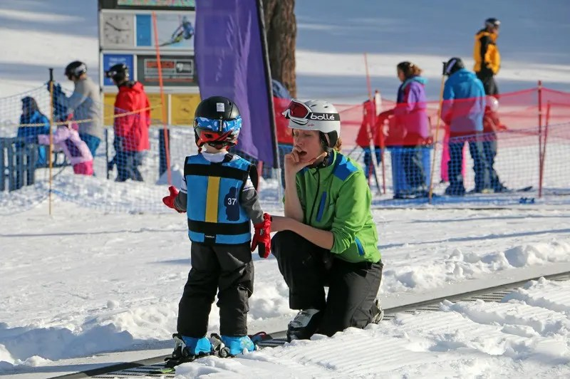 Preschooler talks with his instructor on the magic carpet in his first time in ski school.