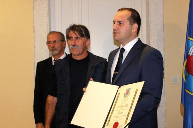 Valerio Bračanov iz ruku načelnika Ivana Klarina preuzima priznanje za MNK Jezera (Foto; Općina Tisno)