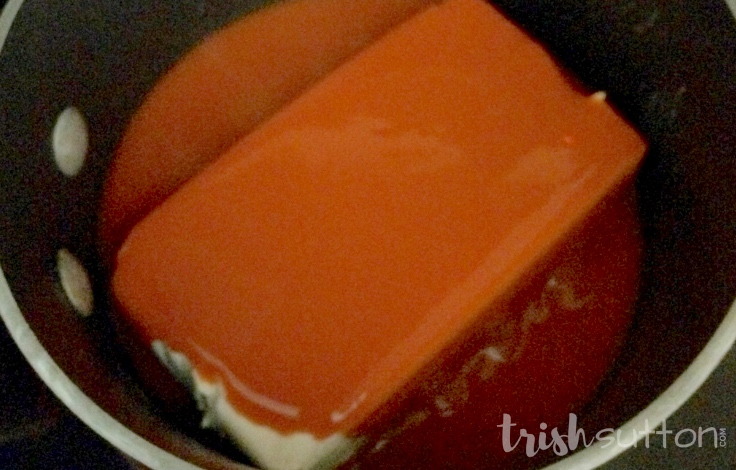 block of cream cheese covered in buffalo wing sauce in a pan