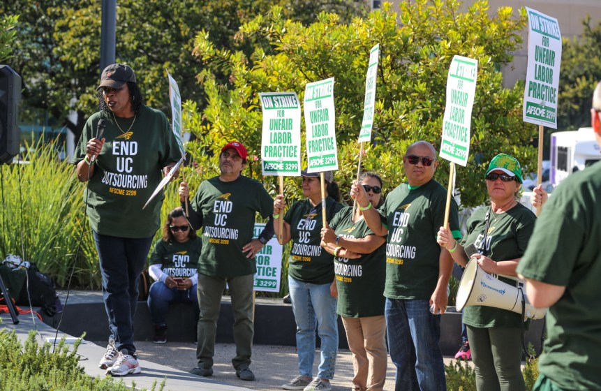 Woman at UC San Diego AFSCME strike delivering a speech with various people behind her holding up signs on November 13, 2019