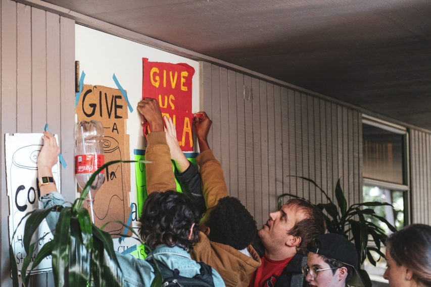 Photo of UC San Diego Graduate Students demonstrating in support of a systemwide Cost of Living Adjustment. Protesters taped signs onto Chancellor Khosla's door.
