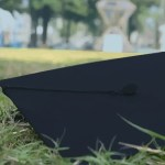 A graduation cap in the grass.