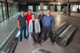UC San Diego connections: (l to r) Eric Soliz,'01; Philip Weinroth, '88; Paul Martini, '01; David Tamjidi, '03, M.S.'05; and professor Gary Gillespie all have ties to the company. Alumni employees not pictured include Aaron Dressin, '00 and Chrisopher Sheddy, '03. (Photo by Xavier Bailey)