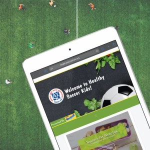 An iPad displaying the 'Healthy Soccer Kids' website.