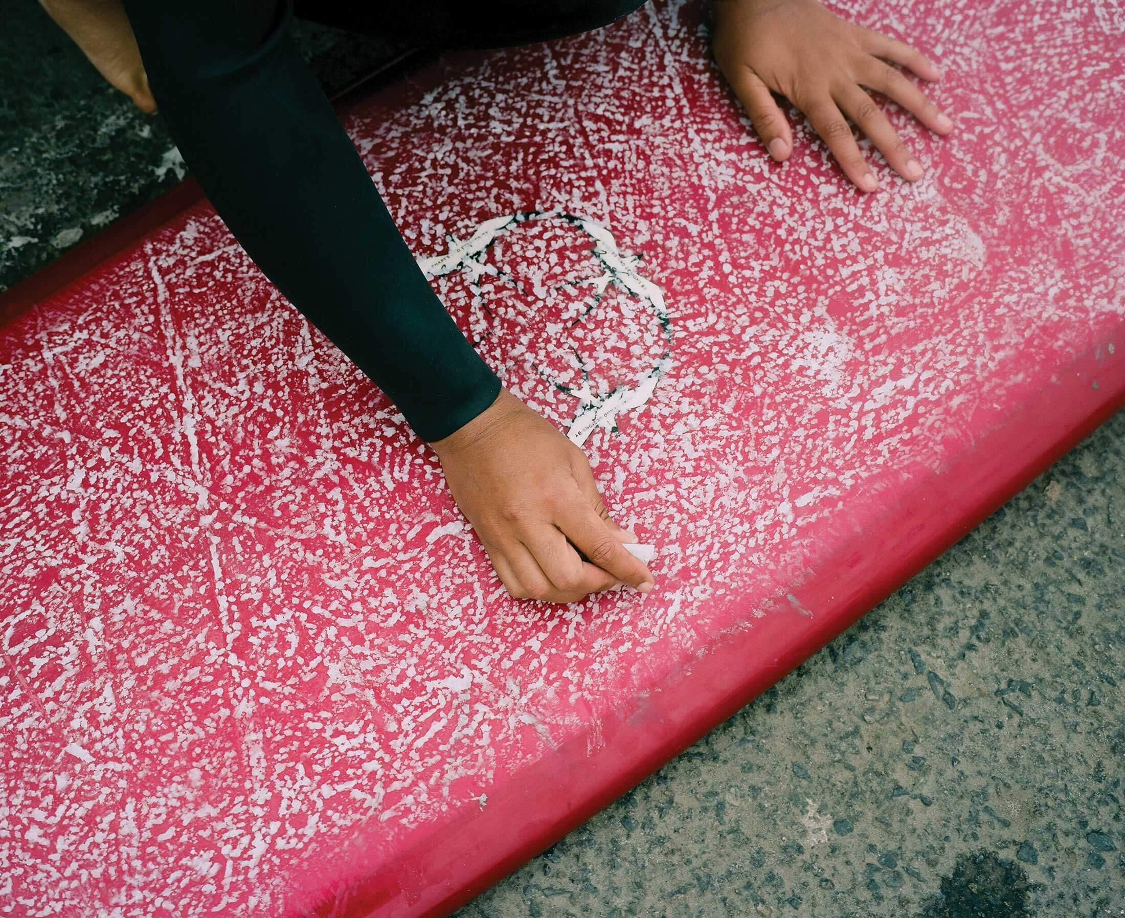 Danielle Black Lyons waxing her board in Oceanside, California.