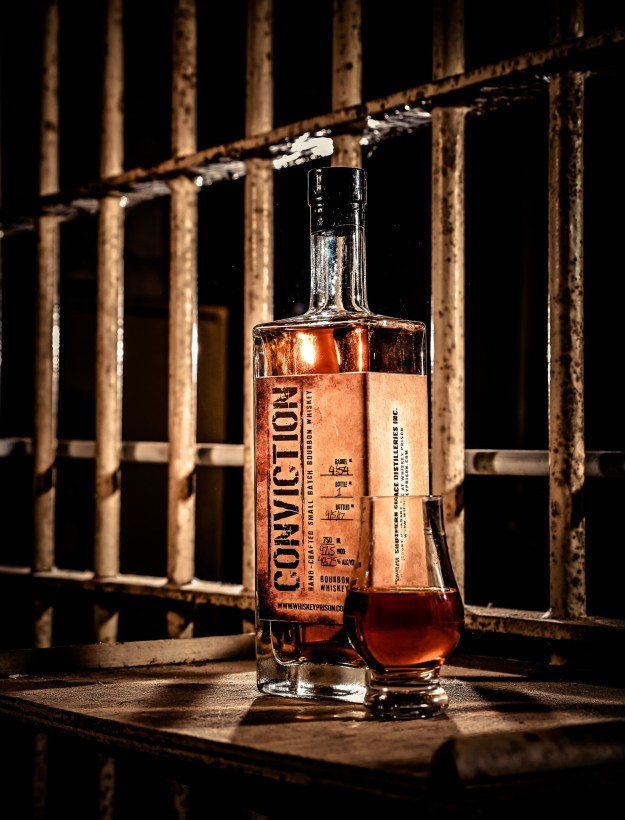 Conviction Small Batch Bourbon behind prison bars. (PRNewsfoto/Southern Grace Distilleries)