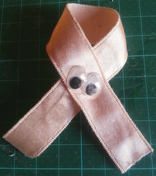 Ett beige sidenband format i en ögla, med två plastögon. Ögonen är av den typ som finns på små leksaksfigurer, och de är fastlimmade över det ställe där bandet korsar sig självt.