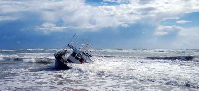white and brown boat on sea under blue and white cloudy sky