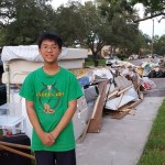 Young man standing next to garbage