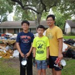 Three boys standing near piled garbage
