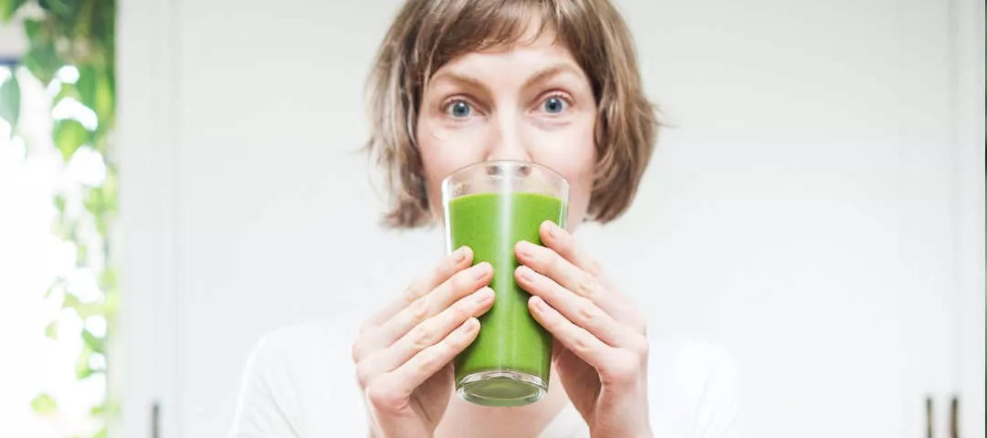Top 10 frozen fruit pulps for wholesale. Image of a woman drinking a glass of Green Juice