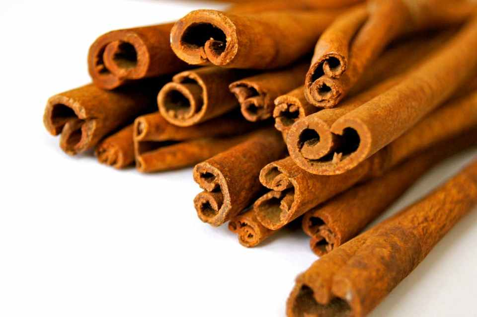a pile of curly tipped cinnamon sticks, on a white background