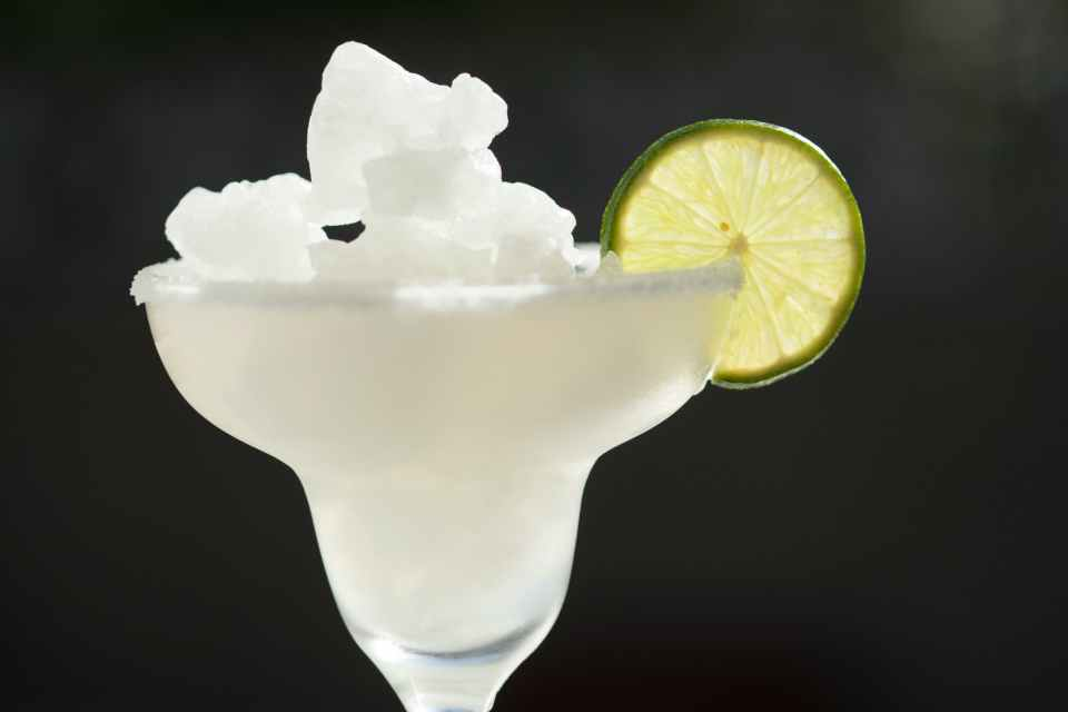 FROZEN MARGARITA IN A MARGARITA GLASS WITH A LIME WEDGE