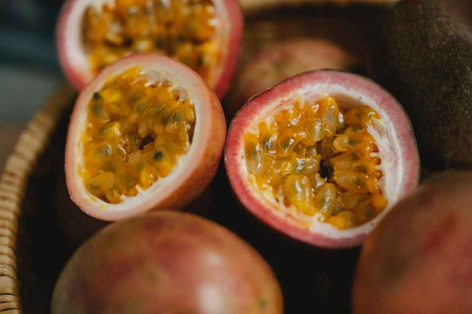 FRESH RIPE PASSION FRUIT, MANY OF THEM IN A WOODEN BOWL WITH A COUPLE CUT OPEN TO DISPLAY THE INSIDES.