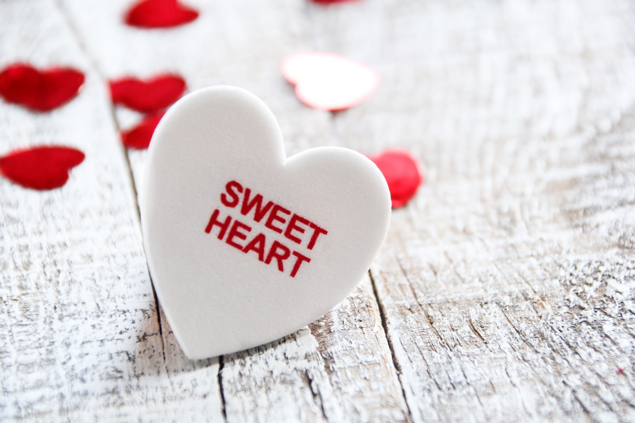 White heart on wooden background with sweet heart text