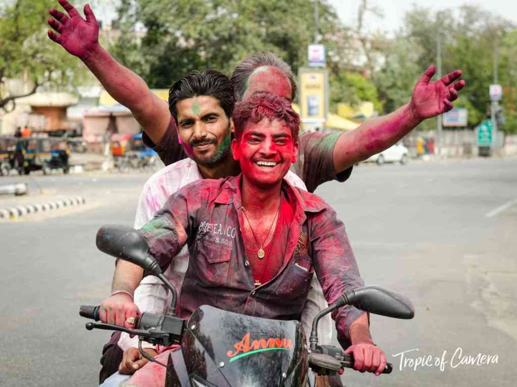 Young men riding home on a motorbike from the Holi festival in Jaipur
