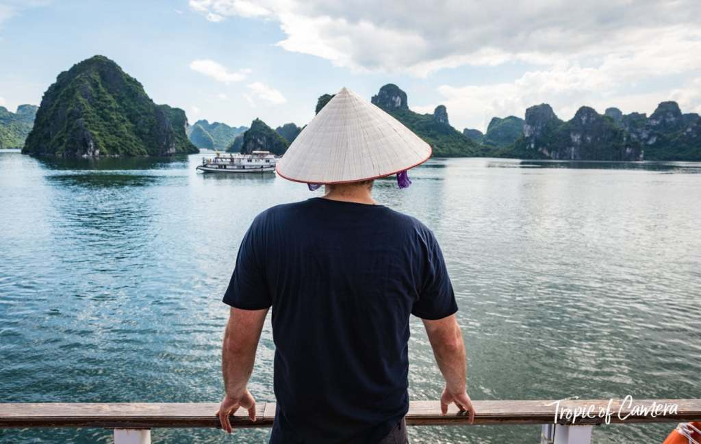 A male tourist in a conical hat looks out on Ha Long Bay, Vietnam