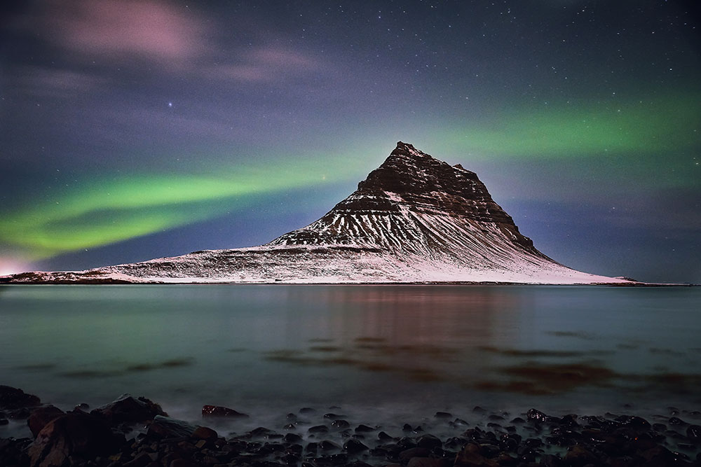 Aurora Borealis behind a mountain in Iceland