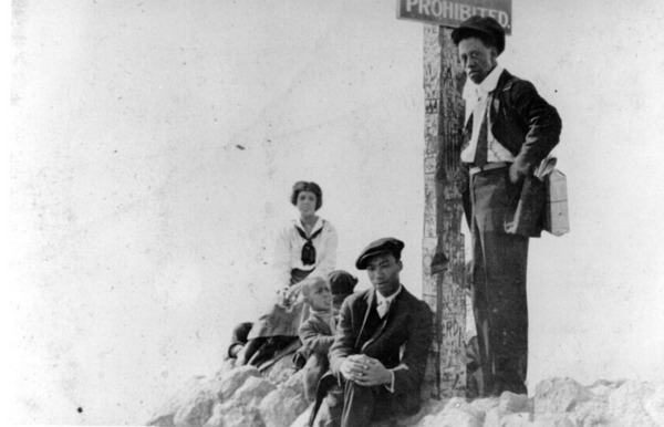 Caption reads: ''A group at the sign that reads 'Prohibited,' at the boundary between Ink Well Beach and the whites-only section of beach in Santa Monica'', ca. 1925. *This caption, which accompanied the donation of the photo, may be inaccurate. See note below, from historian Alison Rose Jefferson | Shades of L.A. Collection, Los Angeles Public Library