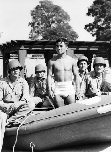 National Diving Champion Sammy Lee in bathing trunks stands in an inflatable boat on dry land. Four soldiers in helmets are in it with him. 1942 | Harry Quillen Collection, courtesy of the Los Angeles Public Library