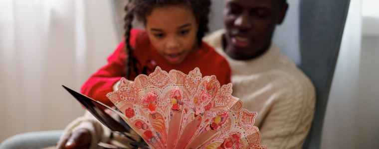 dad and daughter reading a cutouts fairy tale book