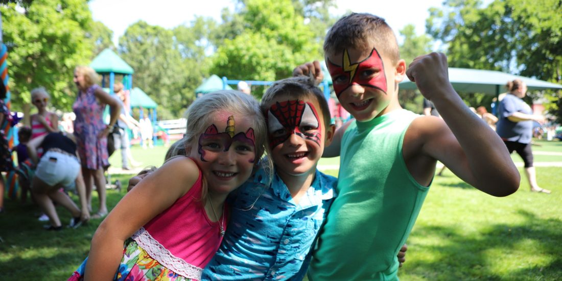 Three children smile with painted faces in a sunny city park with Art at the Park attendees and booths in the background,