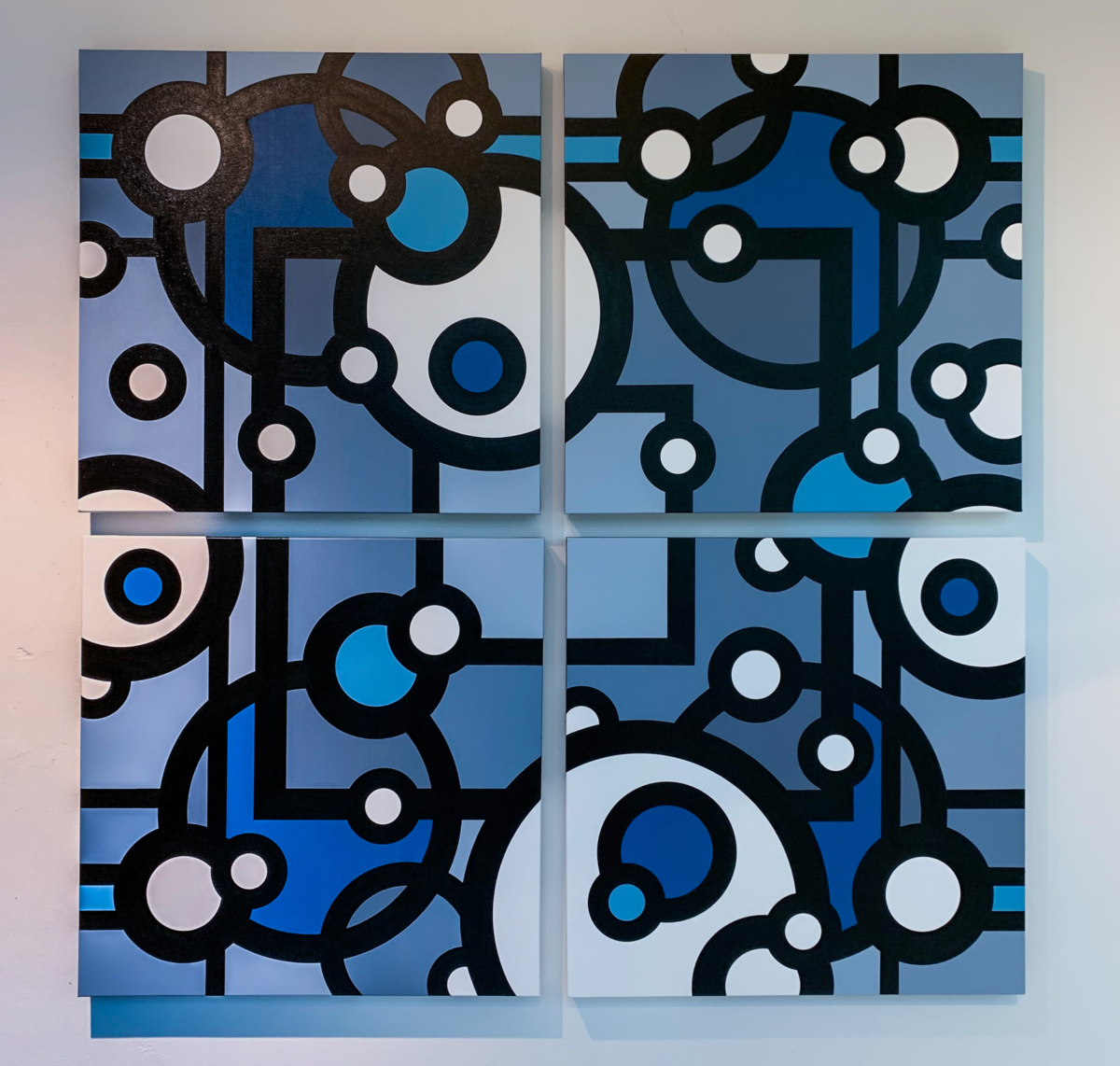 An abstract painting split into quadrants. Circles and squares overlap showing different shades of blue.