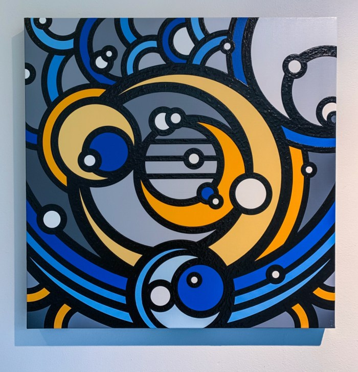Concentric circles of shades of blue and amber create the an image of overlapping crescents.