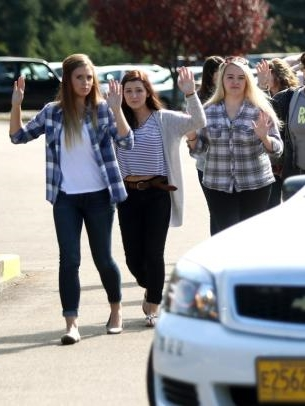 A sad image of high-schoolers being evacuated with hands in their air.